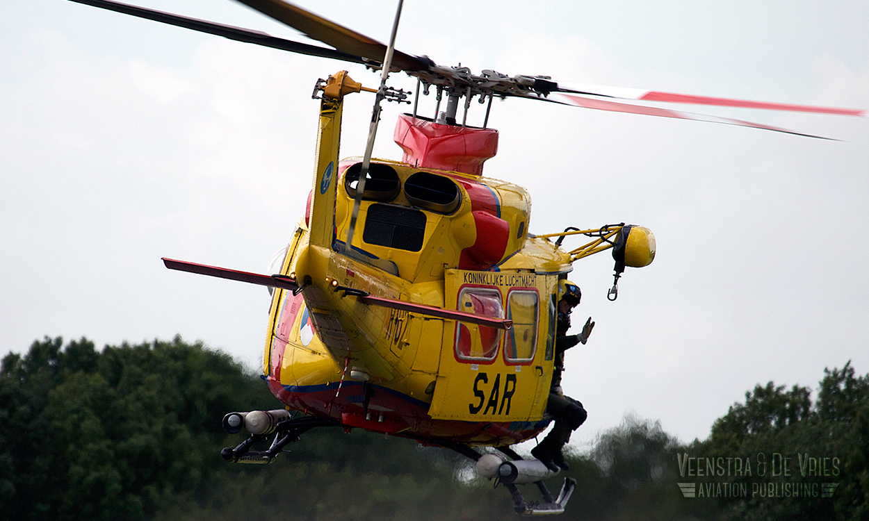 The rescue diver of a RNLAF AB-412SP Search and Rescue helicopter waves at a bystander.  Image copyrighted Lieuwe de Vries - 2014